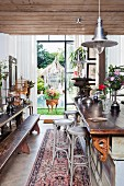 Dining table with long wooden bench and classic bentwood bar stools at counter