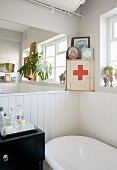 Detail of bathroom corner with bathtub against white, half-height wooden wall and first aid cabinet in corner