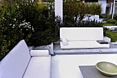 Corner seating with white sofas and table in the garden