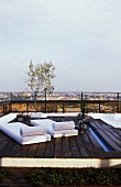 Wooden platform with loungers on a roof terrace with a view across the city