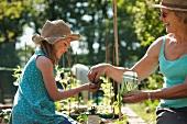 Grandmother handing girl seeds to plant