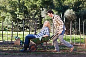 Man pushing girlfriend in wheelbarrow