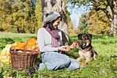 Frau mit Hund unter einem Apfelbaum