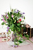 Vase of sweet peas in front of books