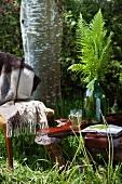 Holztisch im Garten mit Farn