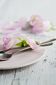 Table place setting - cutlery and Bell Flowers wrapped with a colorful ribbon