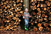 A little boy standing in front of a stack of wood