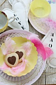 Table decoration with heart-shaped biscuits, feathers and hand-sewn fabric hearts