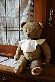 Old teddy bear wearing bib sitting on kitchen dresser in front of lace curtain in glass door