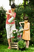 Mother and daughter watering potted plants in garden