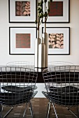 Dining table with metal wire chairs and glossy vase; four square pictures on wall behind