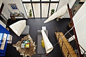 Hängende Objekte über dem Wohnbereich eines modern eingerichteten Hauses mit schwarzem Fliesenboden