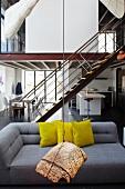 Hängendes Kunstobjekt vor grauem Designersofa mit gelben Kissen in loftartigem Wohnraum