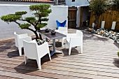 Two bistro tables and modern, white garden chairs next to a small topiary tree on a terrace