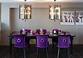 Opulent dining area with silver plated hanging lights and chairs covered in violet velvet at a set, black antique table