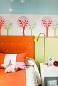 Colorful child's bedroom - orange upholstered headboard and bed linen in front of a tree wall stencil