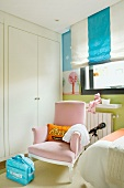 Pastel theme - pink armchair in front of a built in closet and Roman blinds with block stripes in a child's room