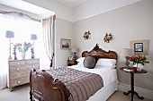 Elegant bedroom; antique bed with bedside table and chest of drawers in window niche
