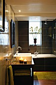 Polished walls and black tiles in bathroom with bathtub and sink