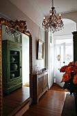 French cabinet reflected in gilt-framed mirror in hallway with bamboo parquet floor