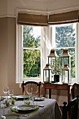 Set table and collection of lanterns in dining room with bay window