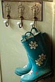 Blue wellingtons with flower pattern hanging from nostalgic metal plate with coat pegs