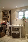 Washstand with legs next to round mirror on delicate metal frame in bathroom; ladder-style towel rack leaning on wall and pretty corner cabinet