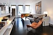 Zeitgenössische Designermöbel im Wohnzimmer mit Sofaecke und dunklem Holzboden