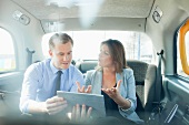 Pair talking business with a tablet computer in a car
