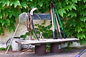 Garden tools on old wooden bench against house facade