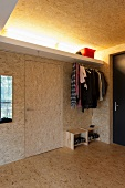 Open-plan cloakroom in foyer clad in chipboard with indirect lighting