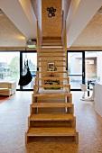 Modern, wooden staircase in open-plan interior