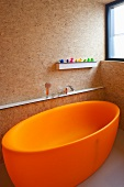 Freestanding, orange bath tub in a bathroom constructed of particle board