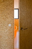 Open bathroom door made of OSB board and a view of a bath tub