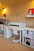 White desk and designer shell chair against wall in room clad in chipboard