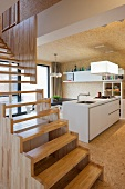 Modern, wooden staircase in open interior with view of kitchen counter