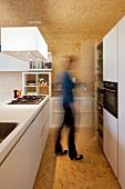 White designer kitchen with island in chipboard-clad room