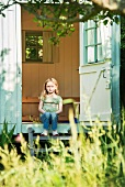 Little girl sitting on the wooden step of a small summer house