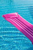 Bright pink lilo in mosaic-tiled pool