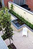 Geometric garden with square beds and elongated pool along garden wall