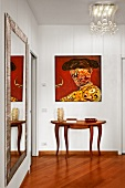 Mixture of styles in hallway - Spanish painting, elegant console table, full-length mirror and designer lamp