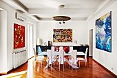 Expressionist paintings provide a visual backdrop for a modern dining table with designer chairs
