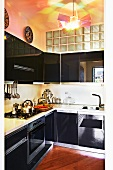 Glossy black kitchen with transom window of glass bricks and contemporary designer lamp