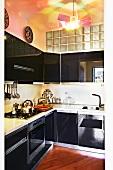 Schwarze Hochglanzküche mit Glasbaustein-Oberlicht und zeitgenössischer Designerlampe