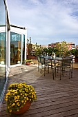 Delicate garden furniture on large roof terrace with wooden flooring