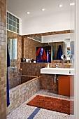 Mosaic-tiled, brown designer bathroom with masonry bathtub and minimalist washstand
