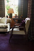 Corner of traditional living room with pale, fifties-style armchairs and art deco table lamp on window sill
