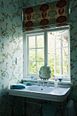 Vintage washstand below window in corner of bathroom with floral wallpaper