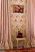 Unusual hat with feathers and red hatband on antique chair against wall with floral wallpaper and striped, floor-length curtains at windows