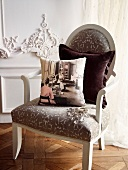 Photo-print cushion and velvet cushion on vintage, upholstered armchair in front of white, carved wooden wall panel. Oak parquet flooring laid in Versailles pattern. Elegant ambiance.